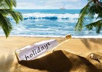 Flaschenpost mit der Nachricht holidays am Strand