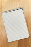 lined notepad on wooden plate