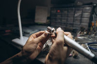 girl master processes the metal plate in the home workshop