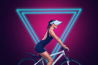 Young woman riding on bicycle in front of modern neon glowing design background