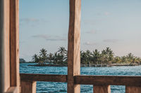 looking through bungalow window on ocean and exotic palm tree island  -