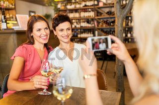 woman picturing friends by smartphone at wine bar