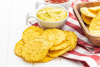 Round nacho chips and avocado dip. Yellow tortilla chips and guacamole in bowl.