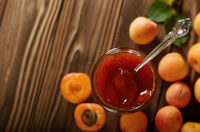 Glass Jar of Apricot jam on wooden table with ripe apricots at background. Top view.