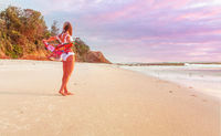 Woman on beach with beach towel flapping behind her