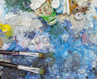 Abstract artistic background from an old palette with paints dried on it.