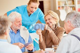 Krankenpflegerin staunend beim Kartenspiel