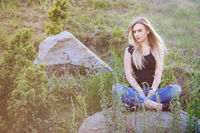 Pensive woman posing sitting on a stone.