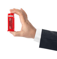 Hand with toy red phone booth of London
