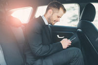 Executive businessman sitting at the back of car using a mobile phone