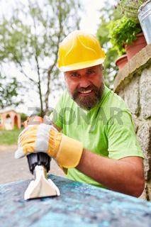 Heimwerker säubert Tisch mit Elektroschaber