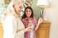 Extremely happy senior woman looking on the pregnancy test of her daughter