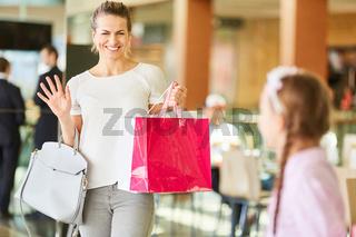 Frau mit Einkaufstüten winkt ihrer Tochter