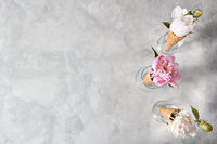Sweet waffle cones with beautiful coloful peony flowers in glass cups on a gray table.