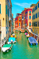 Canal with small bridge and moored boats in Venice,