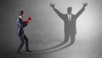 Businessman fighting with a disarmed businessman shadow