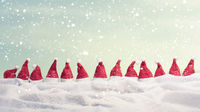 Many hats of Santa in a row with snow