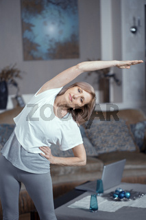 Mature woman bends to the left. Yoga