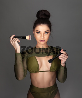 Young beautiful brunette woman holding makeup brushes.