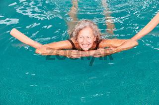Seniorin im Swimmingpool macht Aquafitness