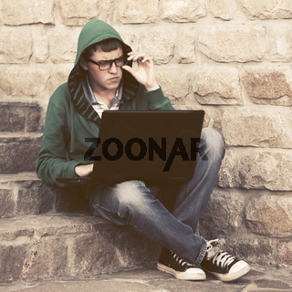 Young man in green hoodie using laptop on the steps