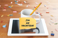 Work and business concept: a cup with a pencil inside on a tablet with a memo and the text I'm on vacation