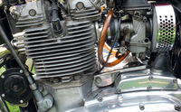 close up side view of a large vintage motorcycle engine with cylinders connecting leads and chrome steel parts
