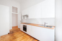 empty, new  built-in kitchen with whote furniture and wooden floor