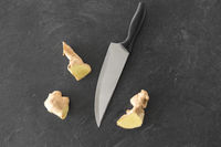 close up of ginger root and knife on stone table
