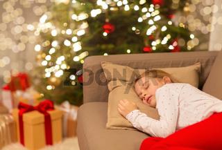girl sleeping on sofa at christmas