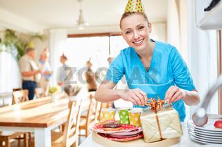 Pflegekraft im Seniorenheim verpackt ein Geschenk