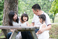 Asian family outdoors with empty table space.