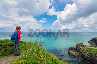 Girl with a backpack on the Cornish coast
