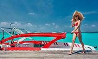 Woman in bikini walking on jetty with boat