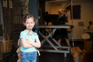 little cute girl standing in front of beauty salon for animals