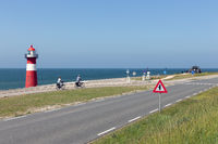 Lighthouse at dike with passing bikers near Westkapelle, the Netherlands