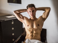 Shirtless naked sexy male model sitting on chair