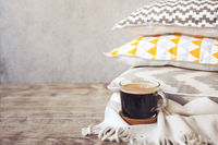 Yellow and grey pillows and cup of coffee on the wall background