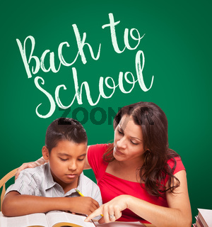 Back To School Written On Chalk Board Behind Hispanic Young Boy and Famale Adult Studying
