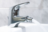Close up of the mixer tap of a bidet with running water. The bidet was invented in France in the late 1700s