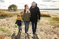 happy family walking along autumn beach