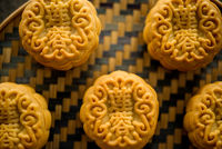 Mooncakes on bamboo background dark light
