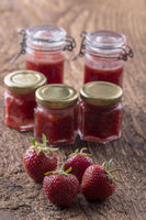 Erdbeermarmelade und Obst auf Holz