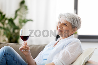 happy senior woman with glass of red wine at home