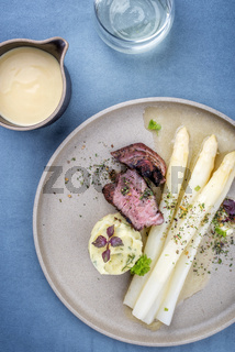 Modern barbecue dry aged sliced fillet steak with white asparagus in butter sauce and mashed potatoes as top view on a plate
