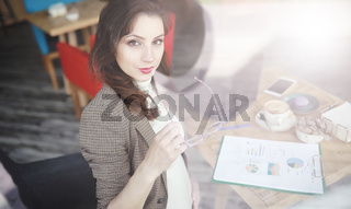 Pregnant woman working on computer in cafe