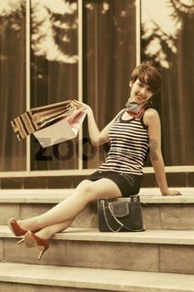 Happy young fashion woman with shopping bag sitting on the mall steps