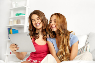 happy friends or teen girls with tablet pc at home