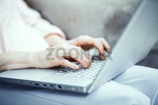 Hands of mature woman typing on laptop