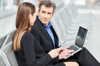 Zwei Geschäftsleute mit Laptop Computer im Flughafen